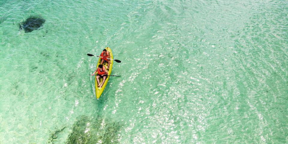 imagen ilustrativa de personas en la playa, pareja en kayak
