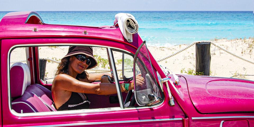 Aventuras terrestres en isla cozumel, chica en un bocho rosa en la playa